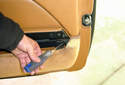 Lift the map pocket flap and at the rear of the door remove the #3 Phillips head fastener that mounts the door panel to the door frame.