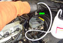This picture illustrates the engine compartment on the left side by the base of the windshield.