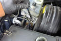 Using an 11mm line wrench, remove the rear brake line from the master cylinder.