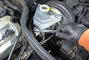 Using an 11mm line wrench, remove the front brake line from the master cylinder.