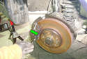 Working at the top of the caliper use a commercially available brake pad thickness tool (green arrow) to measure brake pad thickness.