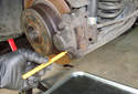 Rear Brake Pads Use the roll pin punch and a hammer to tap out the lower brake pad retaining spring.
