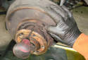 Pull the adjuster out from between the two brake shoe ends.