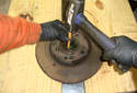 If the seal is difficult to get out you can use two blocks of wood to support the brake rotor and place the brake rotor and hub assembly right side up.