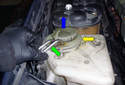 Grab the heating coil (green arrow), pop off the plastic cover (yellow arrow) it passes through and pull upward in the direction of the blue arrow to release it from the washer fluid reservoir.