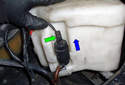 Looking at the front of the washer fluid reservoir, squeeze the electrical connector for the headlight washer system and pull up on it in the direction of the blue arrow.