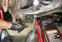 Working at the lower control arm, loosen the lower16mm fastener for the rear shock absorber.