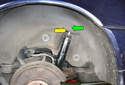 Lower the jack and push the upper shaft of the rear shock absorber (green arrow) down slightly and remove it from the mounting hole in the body (yellow arrow).
