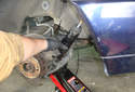 Pull the rear shock absorber upwards to remove it from its mount in the lower control arm.