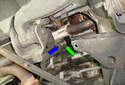 Working at the top of the idler arm mount, tap out the bushing (green arrow) in the direction of the blue arrow.