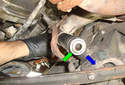 Working from the top of the idler arm mount, insert a drift and push the lower bushing (green arrow) in the direction of the blue arrow to remove it.