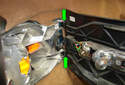 Swing the light bulb panel away from the tail light mounting frame assembly and release it from the hinges (green arrows).