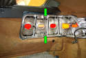 Press the two locking tabs (green arrows) on the tail light mounting frame towards each other to unlock them from the tail light lens.