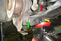 With the jack under the lower control arm, remove the shock (red arrow) bolt from the mounting hole (yellow arrow).