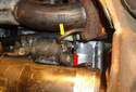 Remove the positive battery cable (red arrow) from the stud on the starter motor.