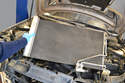 Slide it back out of the plastic air baffle and lift if from the engine compartment.