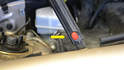 Near the bottom of the left (drivers side) hood shock is a red button (yellow arrow).