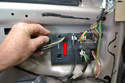 Begin by unplugging the lock wiring connection (red arrow) from the panel on the door.