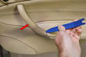 Use your trim removal tool and gently pry the cover of the pull handle (red arrow).