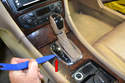 Begin by using your trim removal tool to lift the shifter surround from the panel.