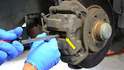 Use a large screw driver between the pad and disk (yellow arrow) to compress the caliper piston back into the caliper.