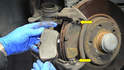 Move to the caliper mounting bracket and remove the two brake pads from their mounts (yellow arrows).