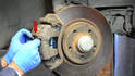 With the piston compressed into the caliper reinstall the caliper over the pads and back onto the bracket.