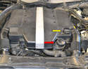 Move to the engine compartment where you will find the oil filter housing (red arrow) as well as the oil filler cap (yellow arrow).