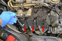 Use a T30 and remove each bolt from the three coil packs (red arrows).