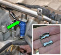 The injector is held onto the fuel rail by a small metal clip (green arrow).