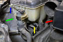 With the air intake removed you can now pull the auxiliary water pump (green arrow) from its mount on the tank (it just pulls straight out), remove the coolant level sensor plug (yellow arrow) along with the wires for the pump and sensor from the bracket (blue arrow) on the front of the tank.