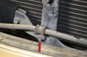 Remove the 10mm bolt (red arrow) that holds the power steering line to the center bracket.