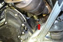 The engine block drain plug is located on the right side of the motor just above the starter (red arrow).
