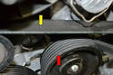 If you look down by the thermostat you can see both sides of the belt; check the backside (yellow arrow) for any signs of cracks or fraying on the sides, on the ridged section of the belt (red arrow).