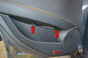Begin by using a T30 Torx and removing the two T30 Torx bolts under the armrest (red arrows).