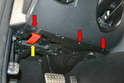 Next, move to the inside of the vehicle, and remove the lower kick panel by removing the three T20 Torx screws (red arrows) along the front of the panel and the Philips head screw holding the hood release in place (yellow arrow).