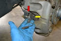 To replace the caliper begin by removing the brake pad wear sensor from the holder (red arrow) by pulling it straight out, and then remove it from the pad (yellow arrow).