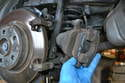 To begin you will need to remove the brake caliper and safely hang it out of the way.