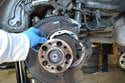 Separate the two parking brake shoes enough so that you can remove them from around the axle.