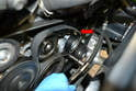 Remove the drive belt by placing a 17mm socket on the tensioner and turning it counter clockwise then slipping the belt off (red arrow).