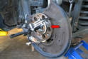 Place a floor jack under the swing control arm and raise the suspension up until the axle is almost level.