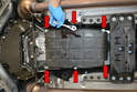 Use an E10 socket and remove the six bolts and hangers (red arrows) holding the pan to the transmission.