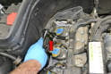 Use an E10 Torx and remove the bolt holding the ground wire in place (red arrow).