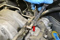 Use a 17mm wrench and separate the fuel line from the distribution rail (red arrow).
