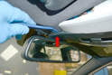 Next, using your trim removal tool, gently pry off the cover at the base of the rear view mirror (red arrow).