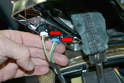 With the trim piece free from the console lift it up and press the tabs on the two electrical connections (red arrows), and remove the connections from the piece.