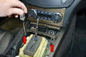 Next, use a T20 Torx and remove the two screws holding the ash tray housing to the center console (red arrows).