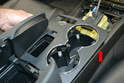 Pry up on the trim piece with your trim removal tool and then slide the trim piece forward and off the console (red arrow).