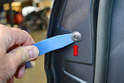 Use a trim removal tool and remove the rubber plug on the inside of the door that is level with the handle (red arrow).