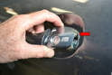 With the screw loose pull the door handle out and then the tumbler (red arrow).